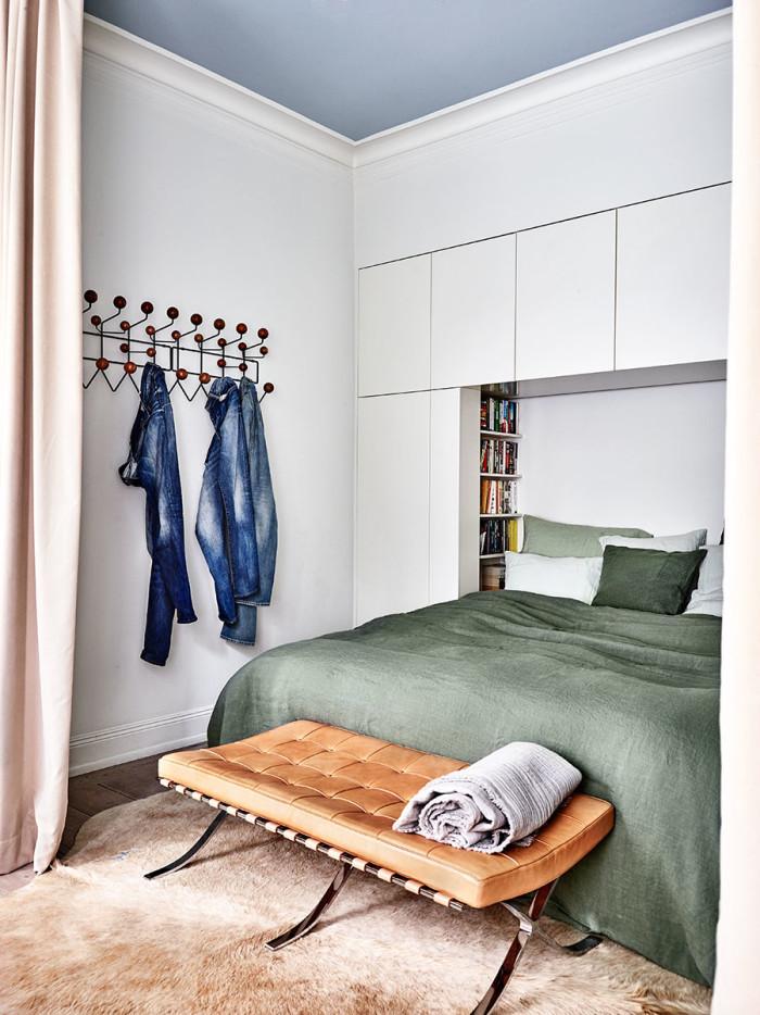 De platsbyggda garderoberna i sovrummet har urtag för bokhyllor vid sängen. Sänglinne, kuddar och pläd från Society, NK Inredning. Vid fotänden står bänken från Mies Van Der Rohes Barcelona-serie, Knoll.