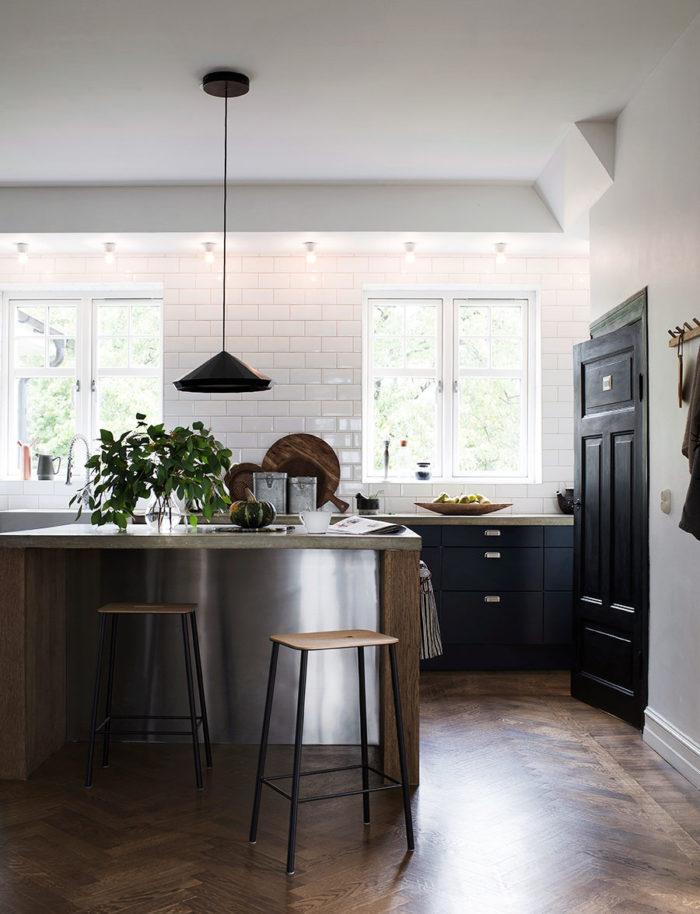 Köket som ligger i norr är inrett utan överskåp för maximalt ljusinsläpp. Köksön är platsbyggd med en bänkskiva i betong och barpallarna kommer från Frama. Köksinredningen är från Ikea men Daniella och Fredrik lämnade in det på lackering och fick ett lite mer personligt, mörkblått kök. Dörren ner till källaren blev en fin detalj när den målades svart.