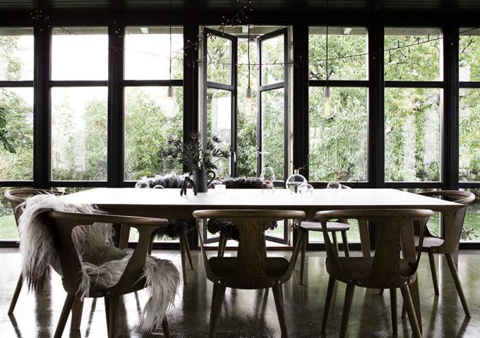 Det svartmålade glasrummet med det magiska lugnet vetter ut mot sädesfälten och trädgården. Bordet är köpt på Lauritz och stolarna är från &Tradition och heter In Between.