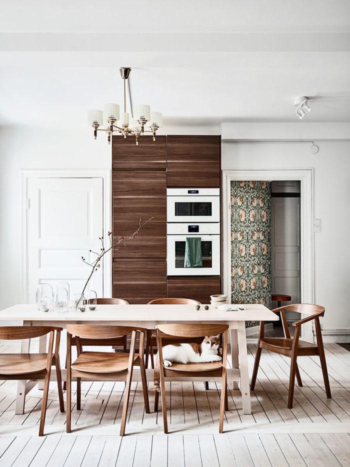De vitmålade väggarna och det betsade plankgolvet ger en perfekt fond åt de varma träslagen i köksinredning och matgrupp. Bord, stolar och köksluckor kommer från Ikea och taklampan är köpt på Antikladan i Lilla Edet. På bordet står loppisfyndade glaskupor i olika storlekar. Tapeten som skymtar i hallen är från William Morris och heter Pimpernel.