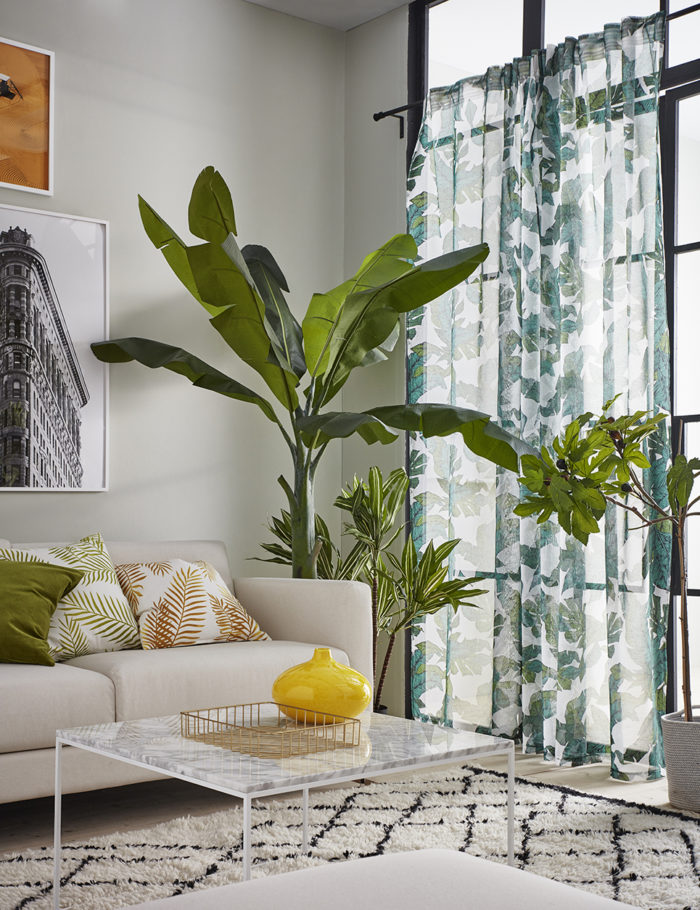 Vardagsrum med bananplanta och fikonträd. Mönstrad matta och gardiner. Jotex vår och sommar 2018.