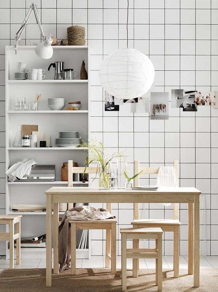 Vitt kök med öppet skåp, matbord och stolar i ljust trä.