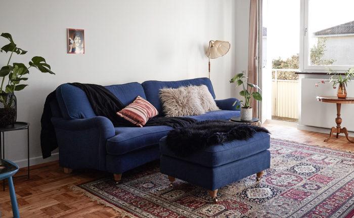 Persisk matta och monstera, blå Howard-soffa med fotpall.