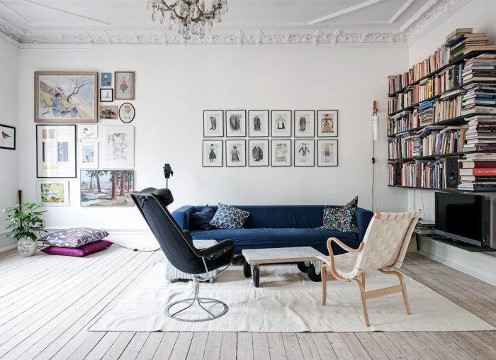 Vitt vardagsrum med stuckatur, tavelvägg och bokhylla. Blås soffa och ljust trägolv.