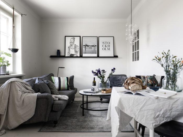 Avskalat vardagsrum i vitt och grått med tavelvägg på tavellist.