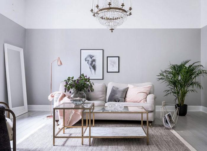 Ljusgrå väggar i vardagsrum med ljus soffa, kristallkrona och rosa prydnadskuddar.