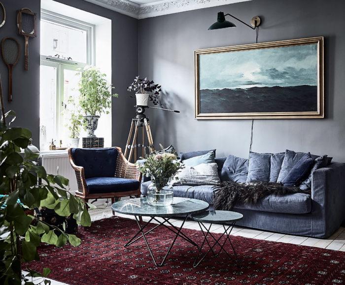 Oljemålning och mörkgrå vägg. Persisk matta i rött och blå soffa.