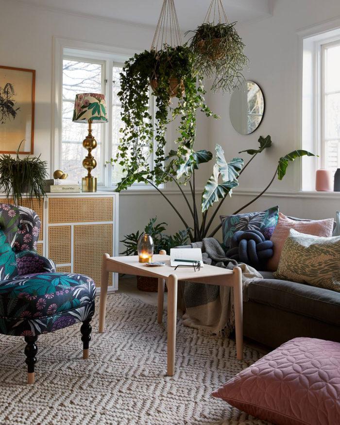 Vardagsrum med mönstrad fåtölj, blandade prydnadskuddar med mönster och i sammet. Ljust träbord, rund spegel, lampa med mässingsfot och matta. Amplar från taket och gröna växter.