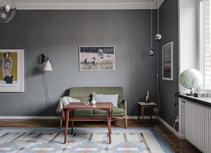 Vardagsrum med grå väggfärg, grön soffa och jordglob i fönstret.