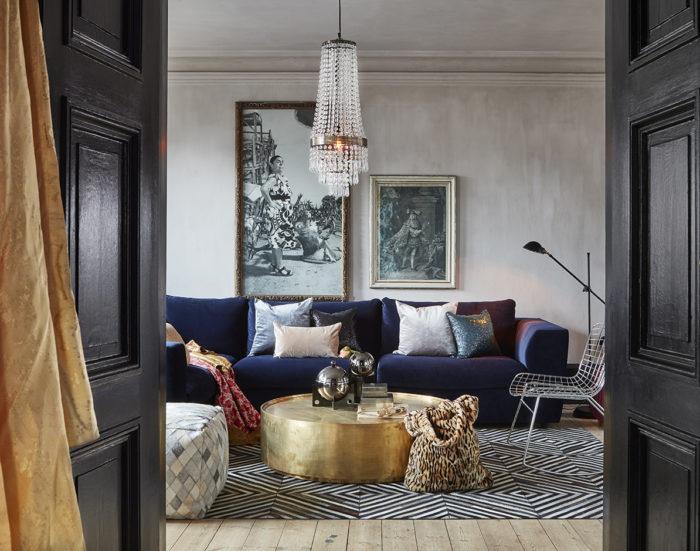 Vardagsrum med kristallkrona, runt mässingsbord, mörkblå sammetssoffa.