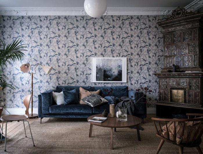Blå sammetssoffa och mösntrad tapet i vardagsrummet.