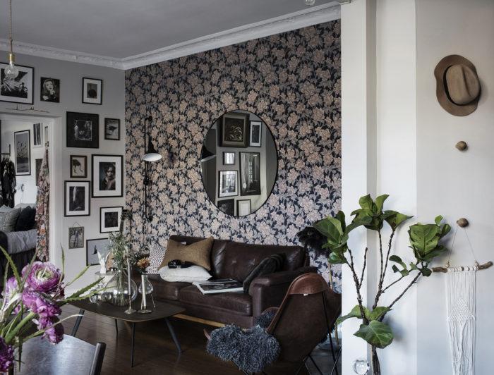 Mönstrad, blommig tapet i vardagsrum med en rund spegel bakom soffan.