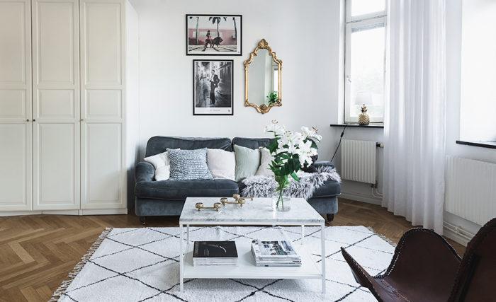 Guldspegel i barockstil bakom soffan i vardagsrummet.