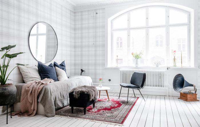 Rund spegel bakom soffan i vardagsrummet.