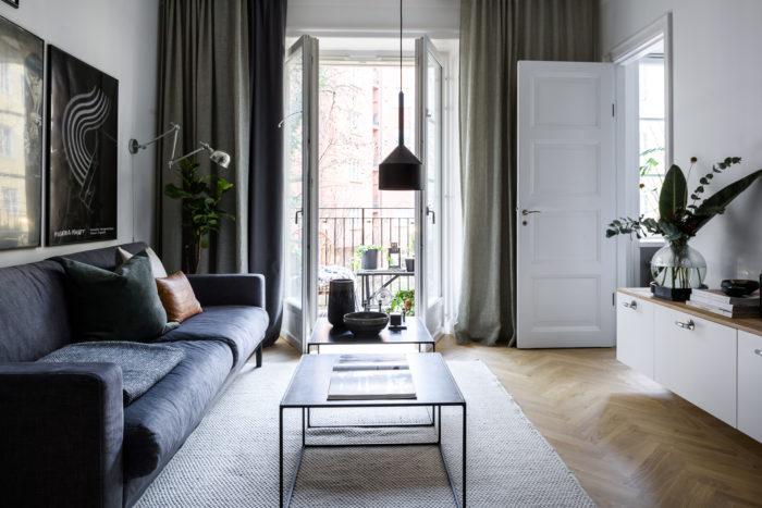 Mörkblå soffa, postervägg och gröna gardiner i vardagsrum.