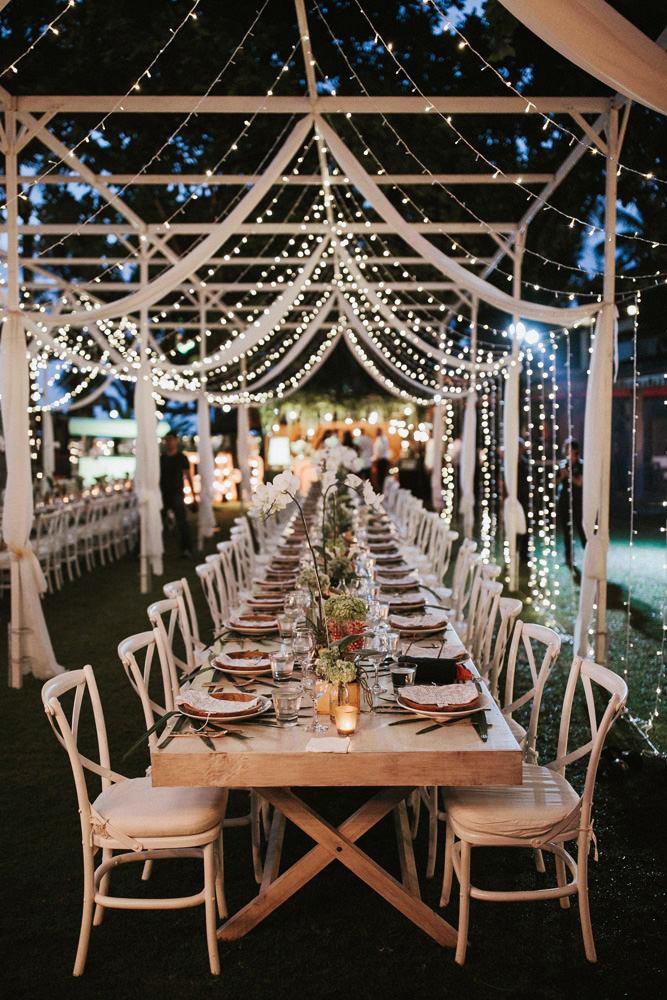 Utomhusbröllop, dukning och plats dekorerad med ljusslingor.