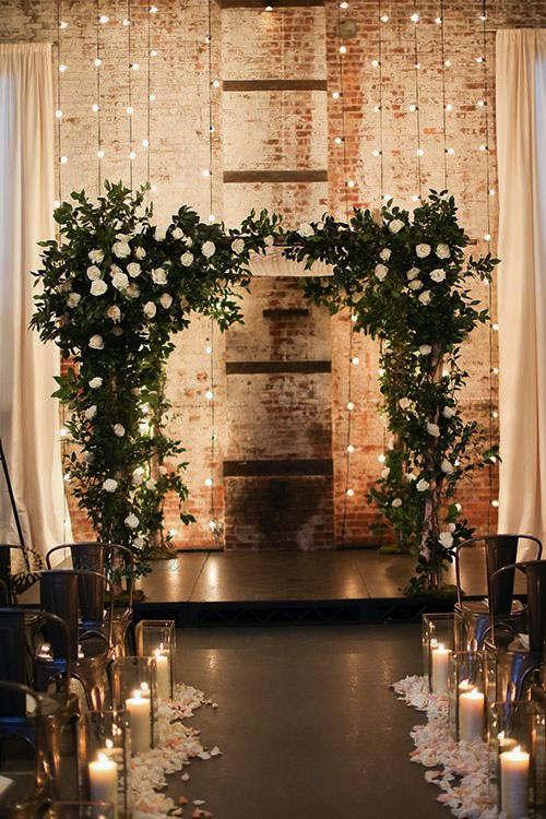 Backdrop med växter och ljusslingor. Bröllopslokal med högt i tak och tegelvägg.