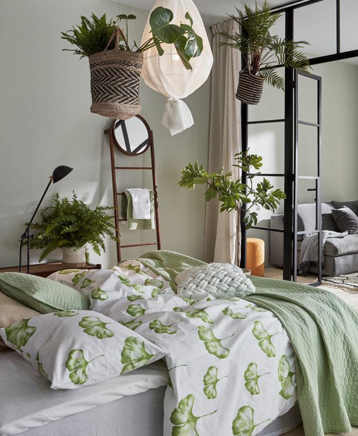 Sovrum med gröna sängkläder och amplar med gröna växter. Glasvägg i industristil. Jotex vår och sommar 2018.