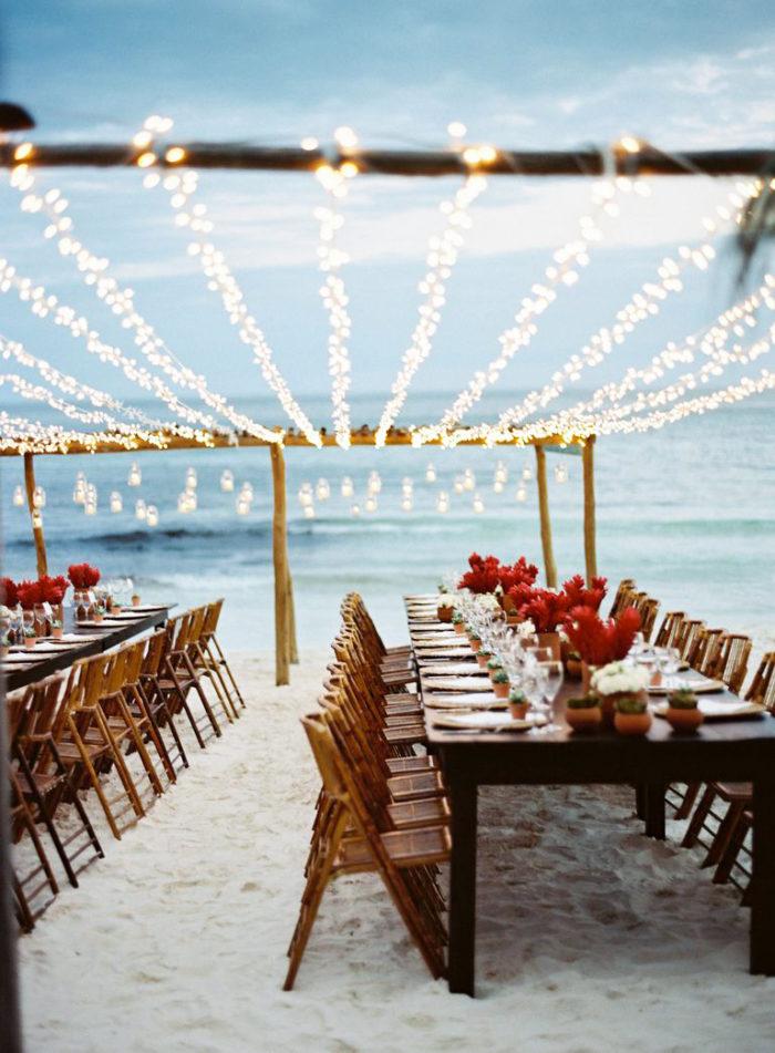 Strandbröllop vid havet, ljus sand och ljusslingor.