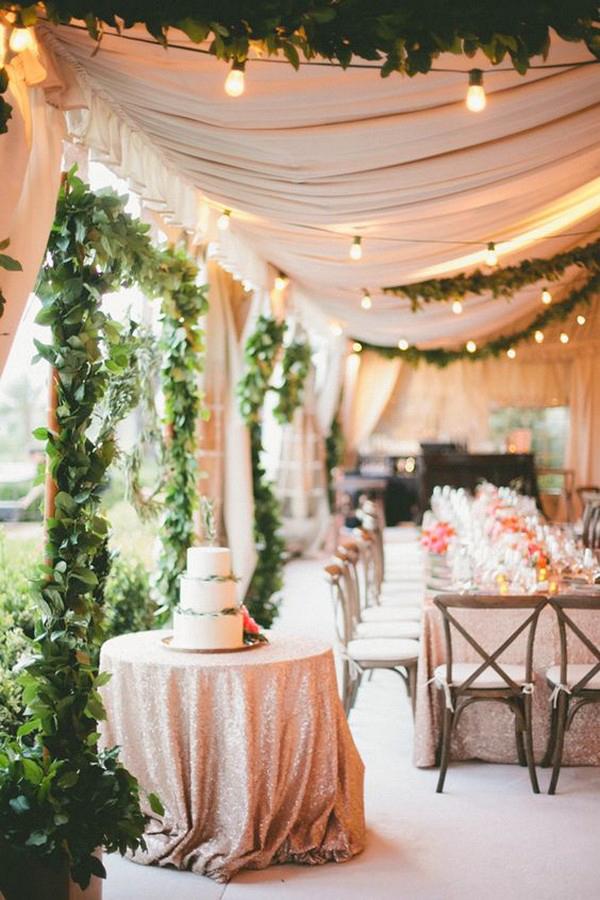Bröllopsmiddag, bröllopslokal med rosa tyger, ljusslingor och gröna växter som dekoration.