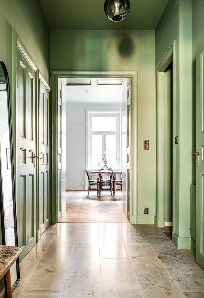 Green painted ceiling and walls in an apartment in Stockholm. Scandinavian styled hallway.