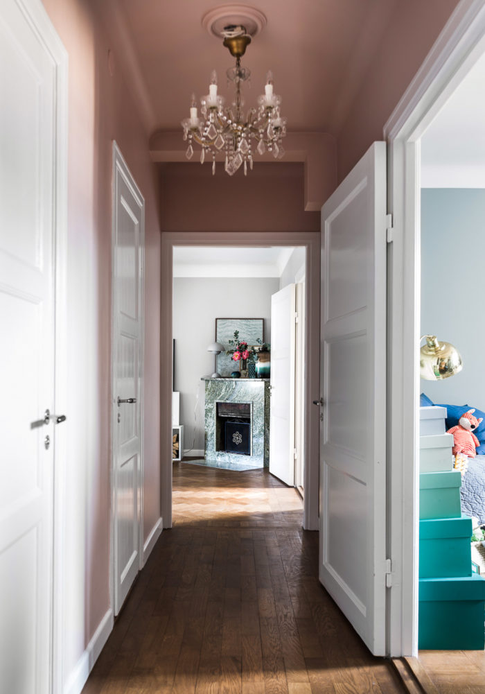 Pink painted ceiling and pink walls in an apartment in Stockholm. Scandinavian styled hallway.