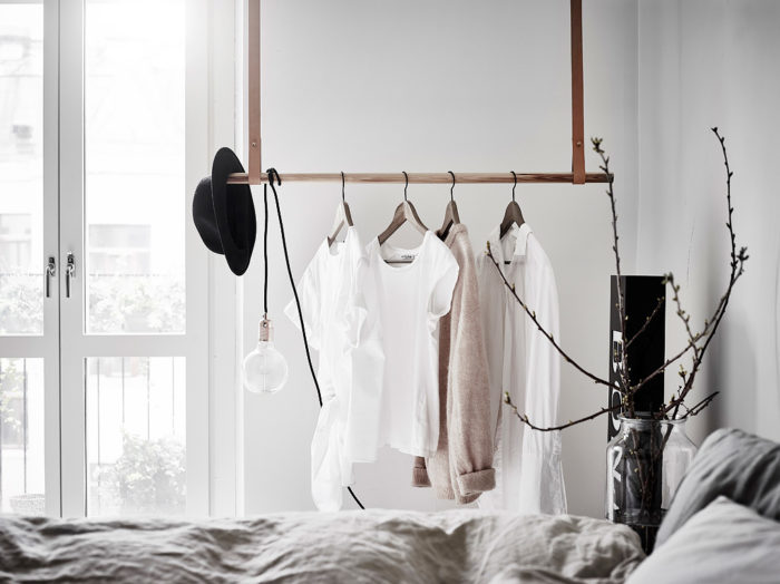 Cosy bedroom with hangers and leather handles. Scandinavian style.