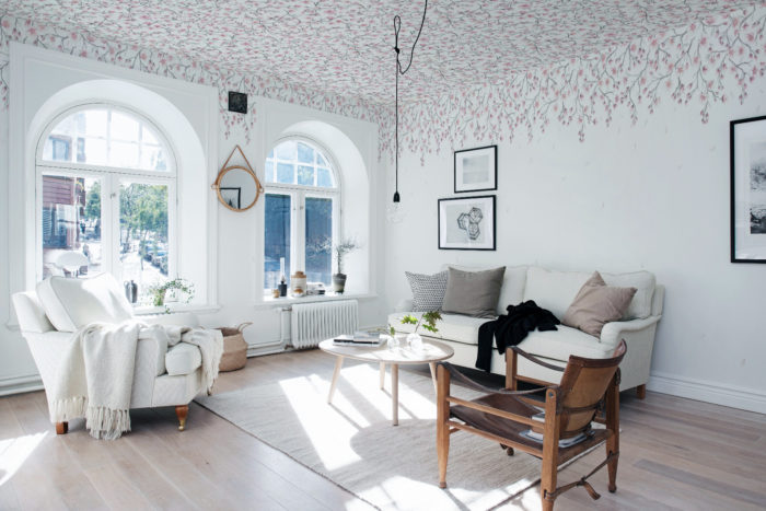 Wall paper in the ceiling. Scandinavian styled livingroom with floral wall paper in the ceiling.