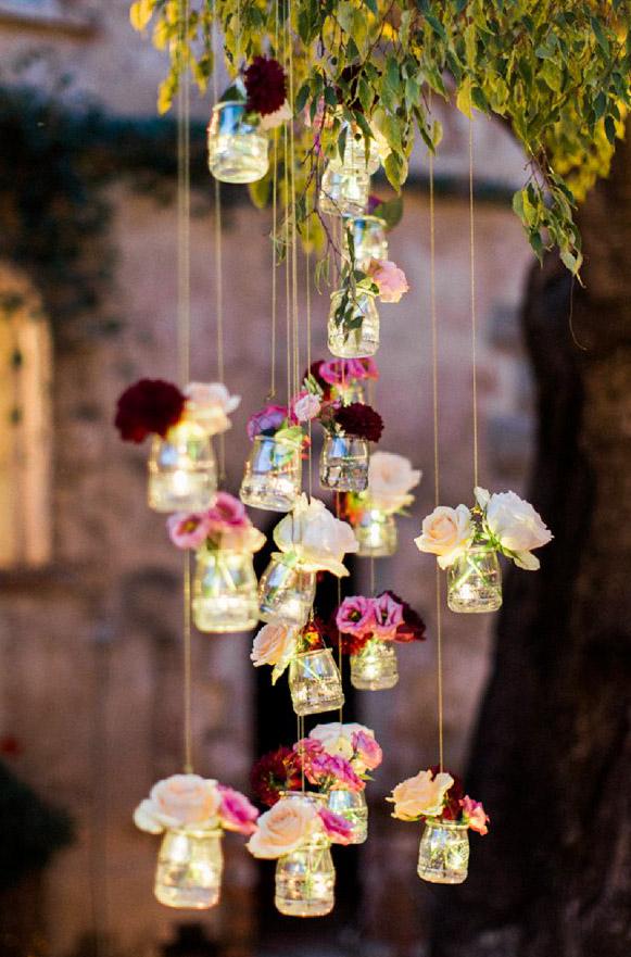 Glasburkar upphängda i träd, med blommor. Trädgårdsbröllop.