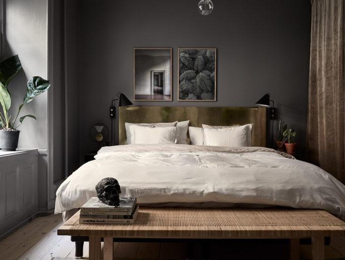 Sovrum med målade mörkgrå väggar, färg Mole's breath från Farrow & Ball. Sänggavel i mässing, tavlor ovanför sängen och rottingbänk från Ikea Stockholm 2017.