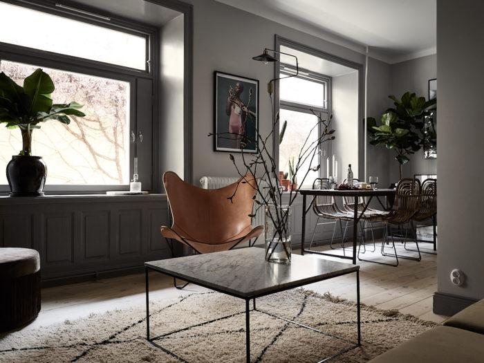 Stilfullt vardagsrum med grå väggar och snickerier. Fladdermusfåtölj i läder, marmorbord med svart underrede.