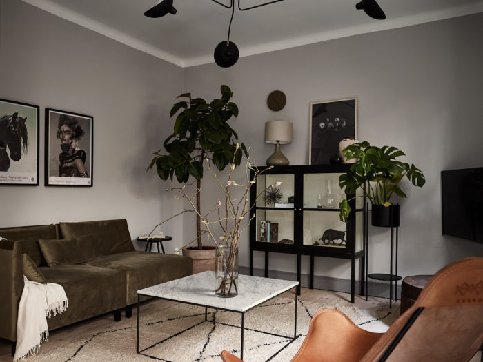 Vardagsrum med gråmålade väggar, svart grafisk taklampa, läderfåtölj, soffa och sittpuff i sammet. Fönsterfikus och monstera, marmorbord med svart underrede.