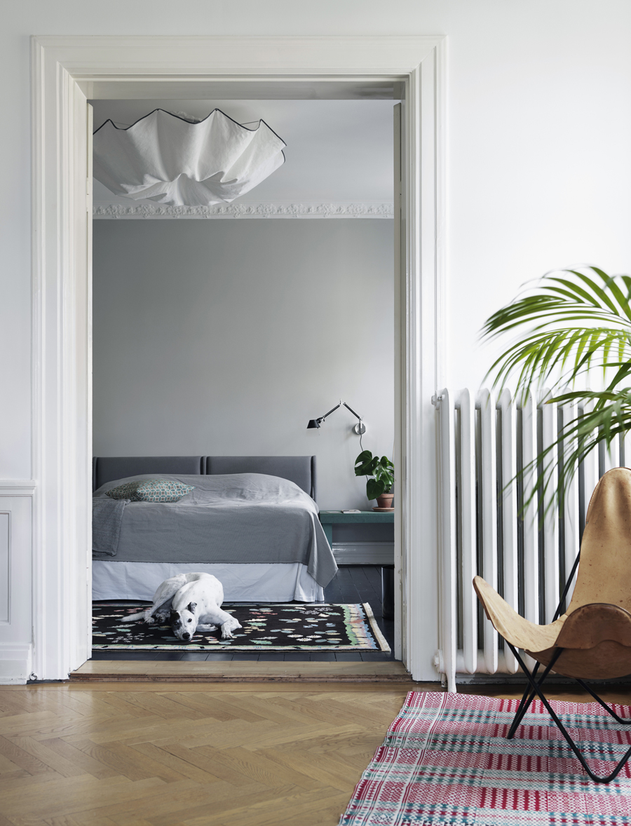 sovrum med fin taklampa och textiler