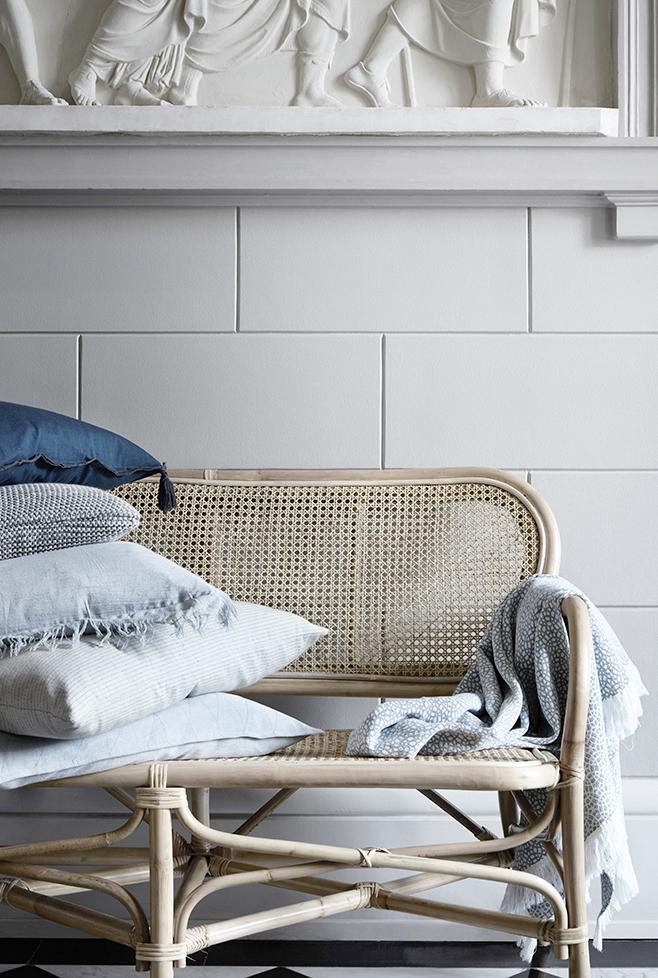 Rattan sofa with pillows.