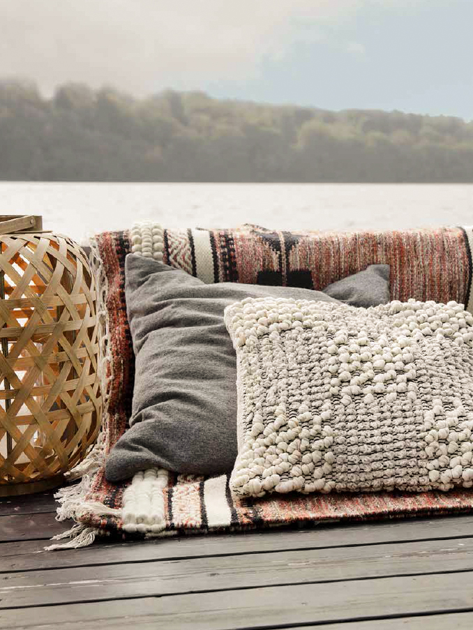 Pillows and rug placed outdoor in the summer.