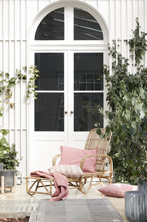 Rattan chair with pink pillows and a throw.
