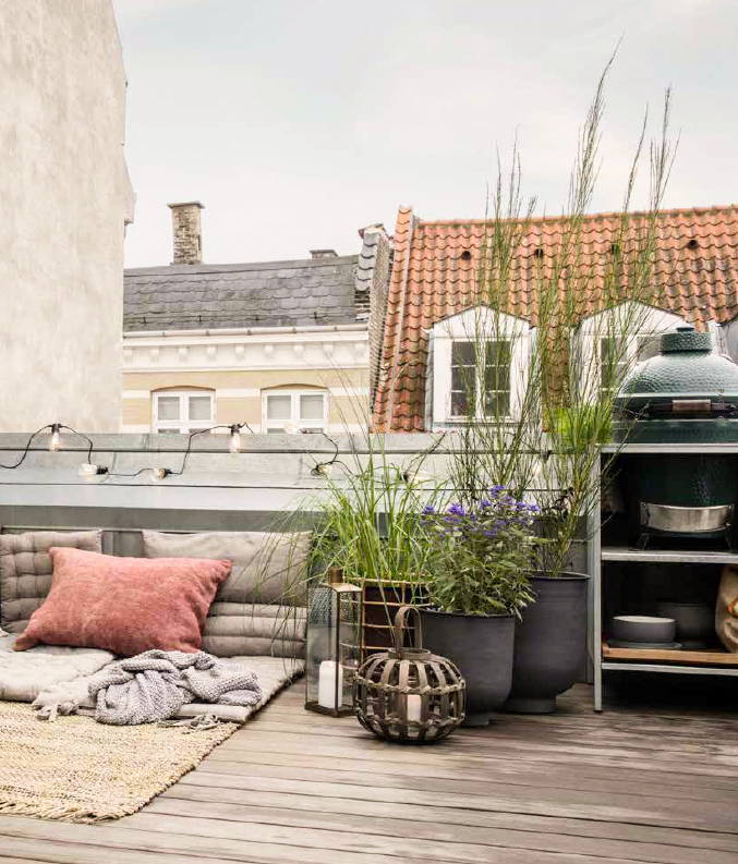 Cosy balcony with plants and pillows.