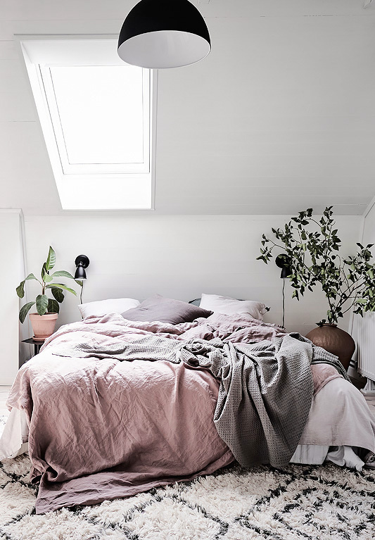 Bedroom with pink linen and green plants.