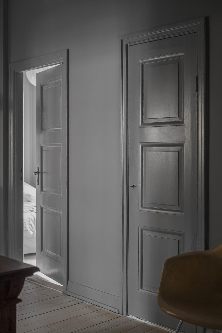 två dörrar målade i samma gråa färg som väggen
