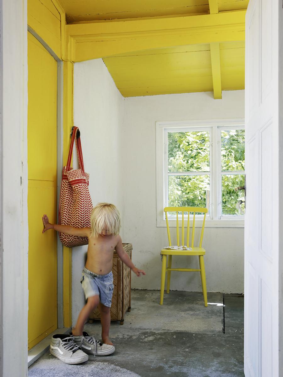 Bobo provar skor. Väskan som hänger på väggen kommer från Becksöndergaard och den gula stolen är ett fynd från Myrorna.