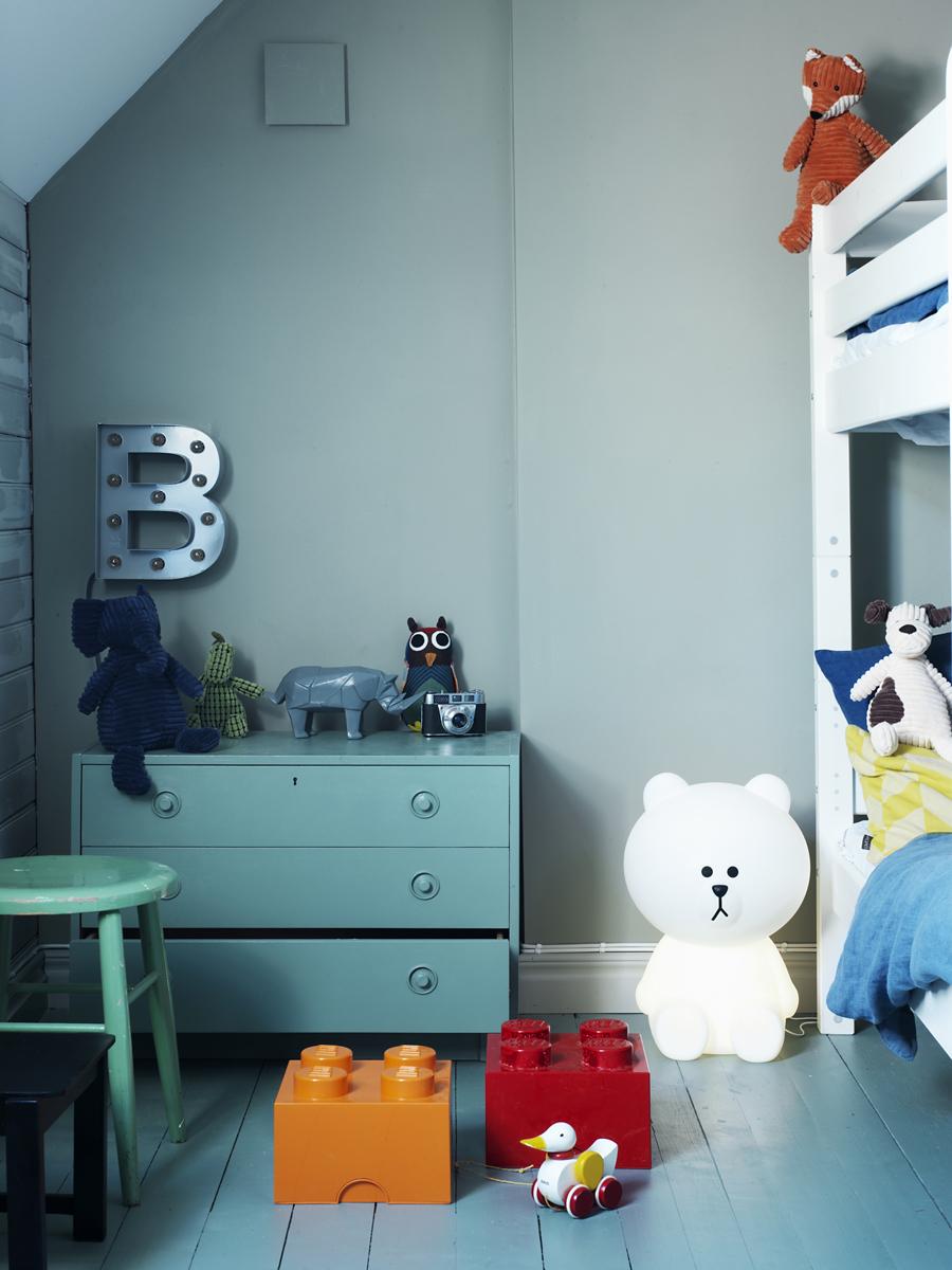 Våningssängen maximerar utrymmet i barnrummet. På väggen hänger en B-lampa från pappas Cirkuslampan.se. Byrån och pallen är loppisfynd, lådorna på golvet kommer från Lego och björnlampan från Jollyroom.
