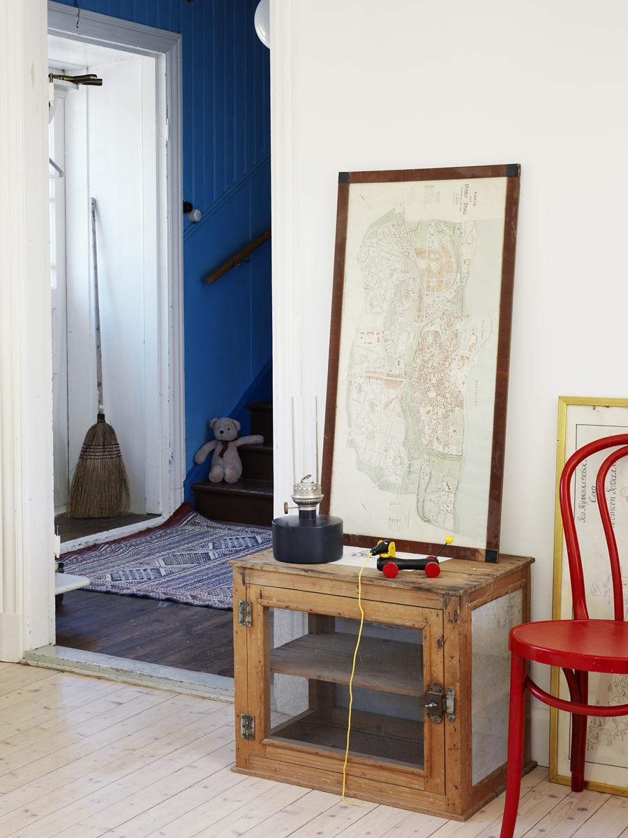 Huset är fyllt av charmiga loppisfynd som den röda stolen och skåpet som de hittade på juliloppisen i Hellvi. Tavlorna fanns på gården när de köpte huset.