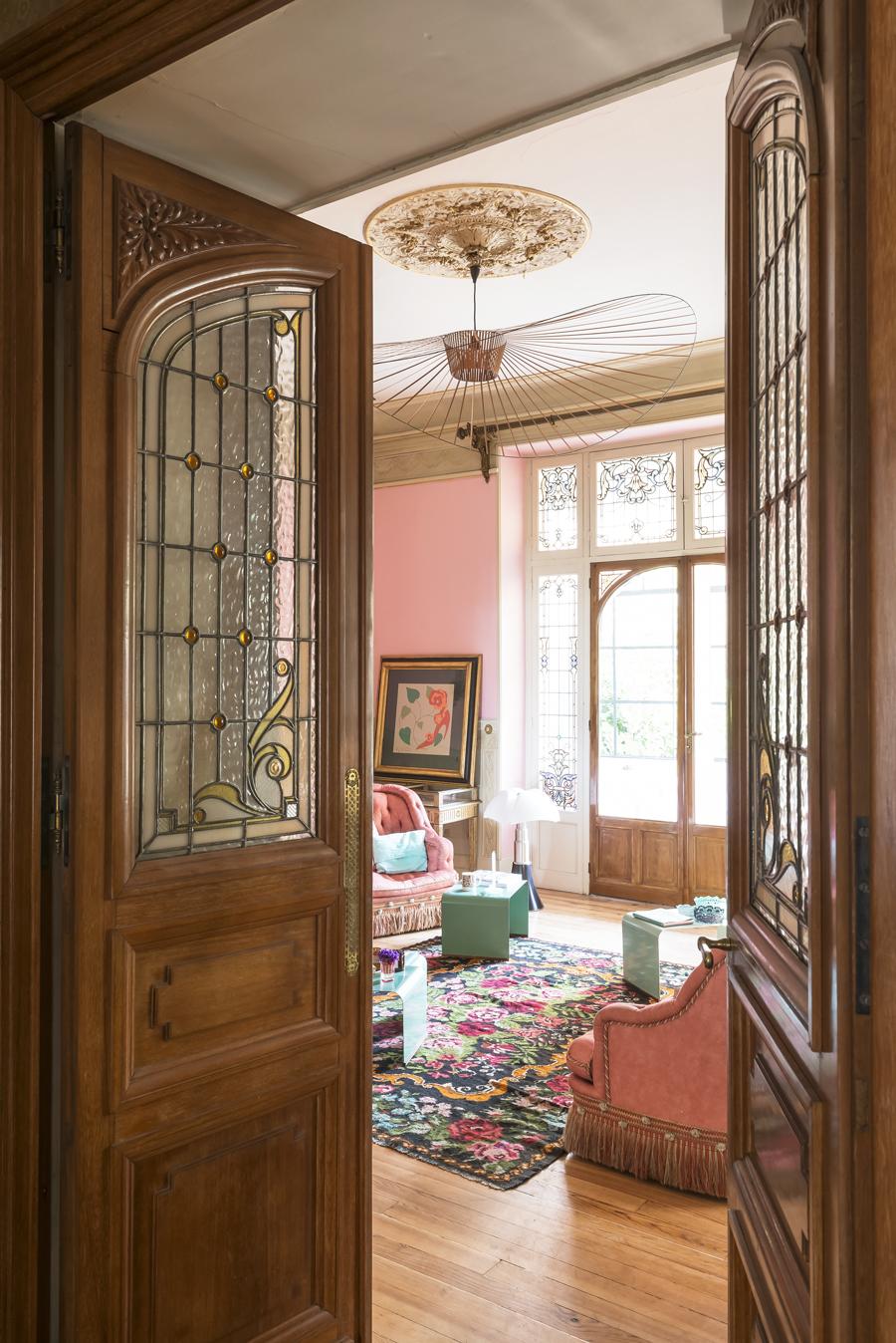 Dubbeldörrar i glas delar av det tvådelade vardagsrummet där Lisa och Julien inrett var sin sida.