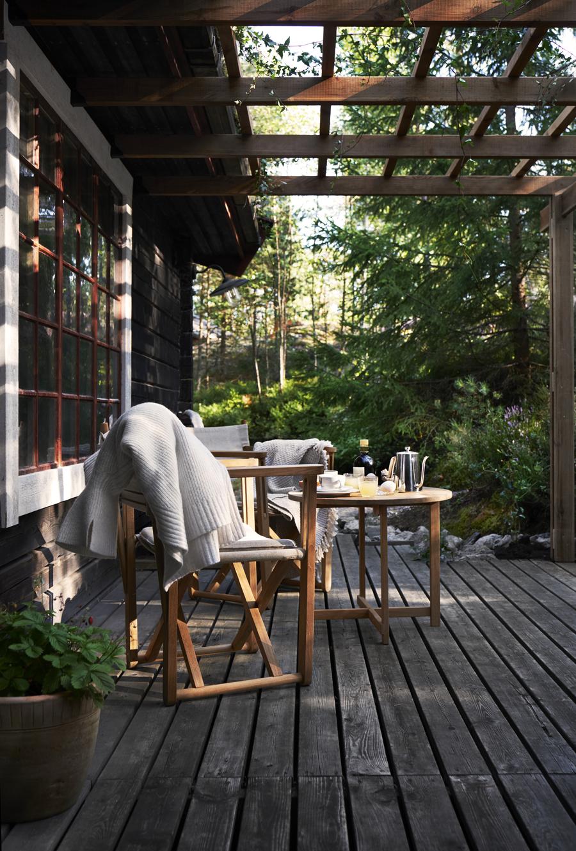 Uteplatsen under pergolan har sol på eftermiddag och kväll. Bordet och stolarna i teak och linne är modell Kryss från Skargaarden. Tanken var att fortsätta på safari- och regissörsstolstemat, som även återfinns inne i huset.