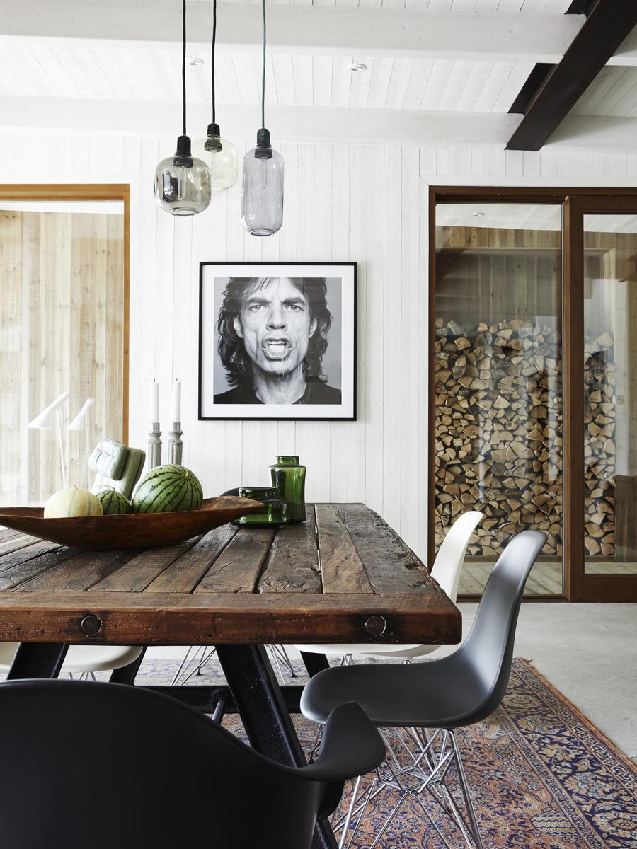 Det tunga bordet är köpt på en utförsäljning, underredet är från en gammal järnväg och passar fint ihop med järnbalkarna i taket. Stolarna är Eames DAW och DSW, Vitra. Ljusstakarna på bordet är Tove Adman och vaserna är fyndade på gotländsk loppis. Mick Jagger är fotad av Patrik Andersson.