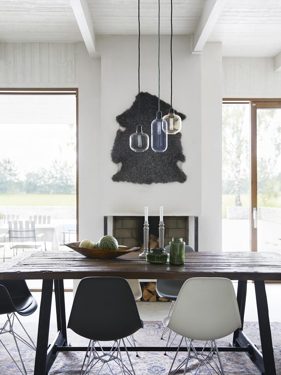 Matbordet har ett underrede från en gammal järnväg. Stolar DAW och DSW, design Ray och Charles Eames, Vitra. Taklampor från Normann Copenhagen.