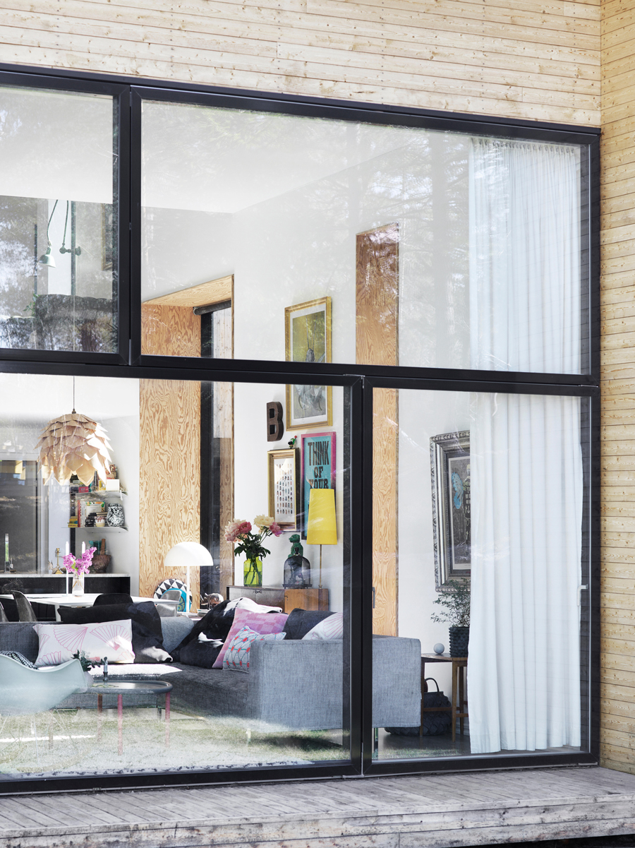 Vy från utsidan av huset som är klätt i ljust trä för en ren look. Huset har generösa fönsterpartier som påminner om svarta kassetter.