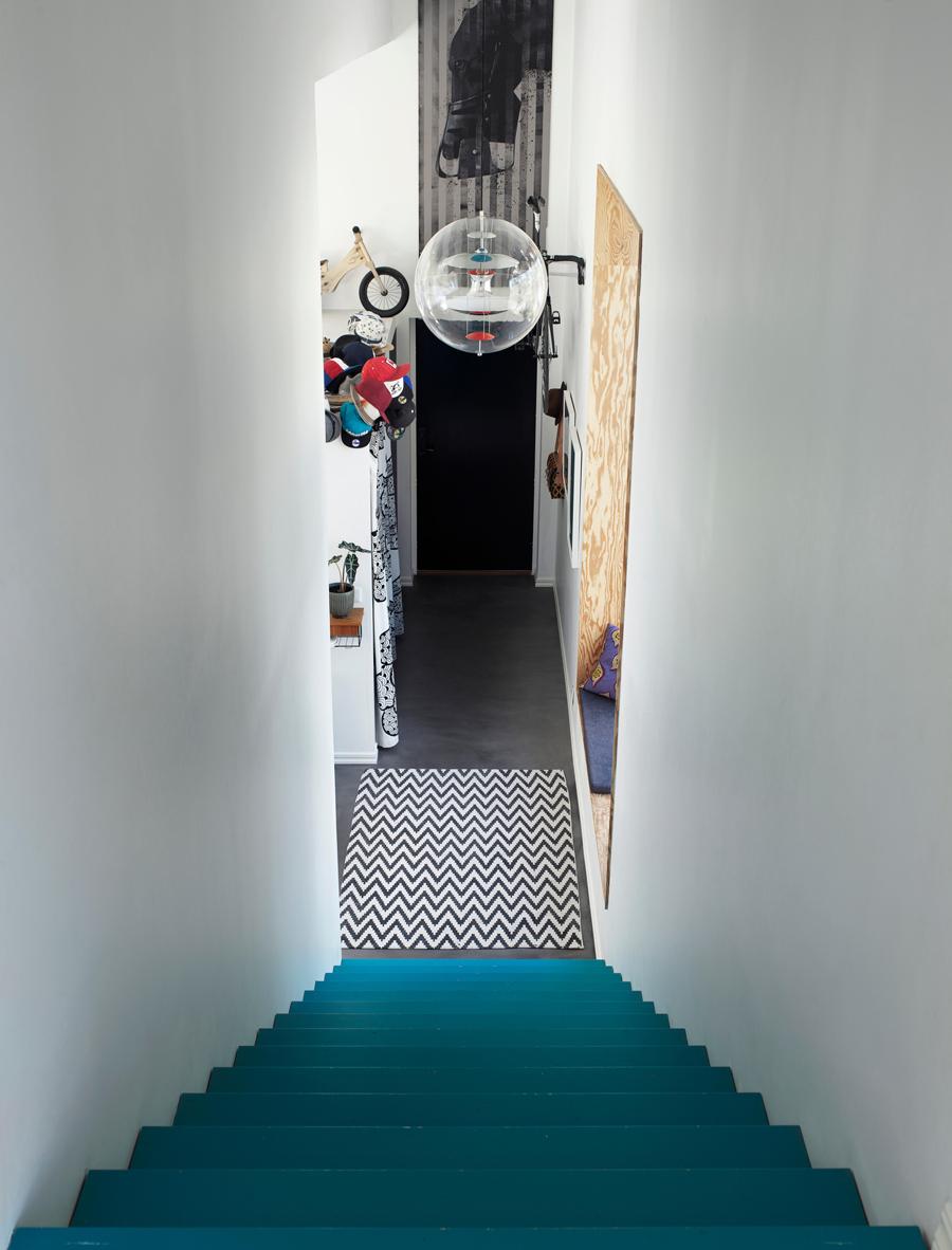Den blå trappan är en av många detaljer att lägga ögonen på i huset. Historien bakom är att familjen ville skapa en kostnadseffektiv och slitstark trappa och valde målad furu. Taklampa, Verner Pantons Globe, Verpan.