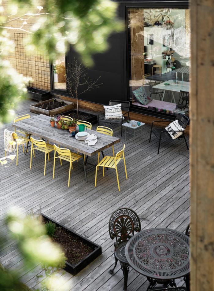 På uteplatsen med tillhörande kök finns plats för stora sällskap och tillställningar. Generöst matbord och ett platsbyggt utekök. Gula stolar, Ikea.