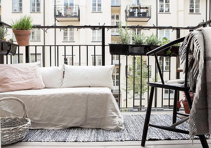 Balcón escandinavo con cama cubierta de lino.